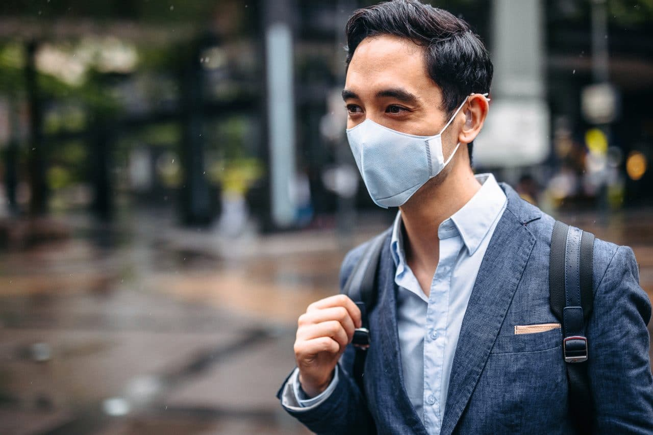 Businessman wearing pollution mask in city